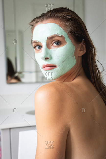 Close-up of beautiful woman with facial mask sitting in the bathroom
