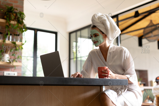 Woman with coffee cup using a laptop in the kitchen after having bath in the morning
