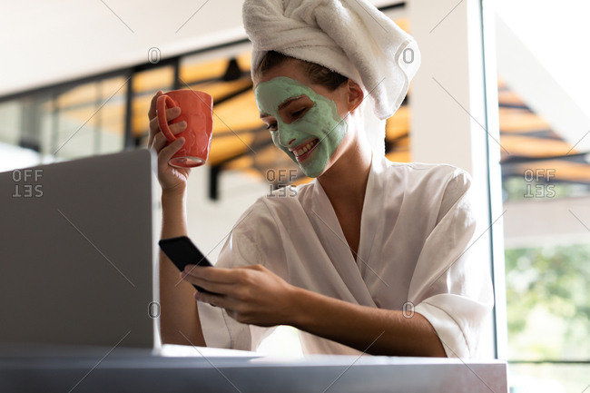 Smiling woman in bathrobe checking her phone while having coffee
