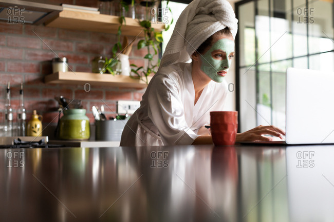Beautiful woman in bathrobe using laptop on the kitchen counter at home