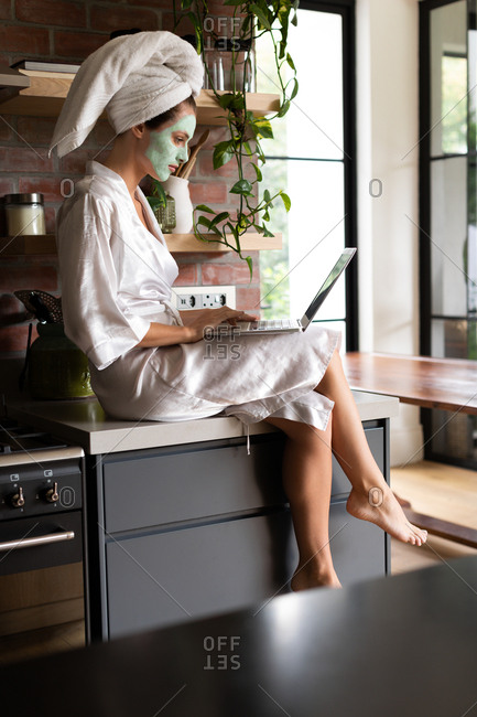 Woman in bathrobe sitting on the kitchen counter and using laptop in the morning