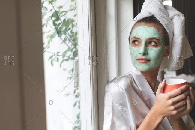 Beautiful woman in bathrobe wearing facial mask, looking through the window