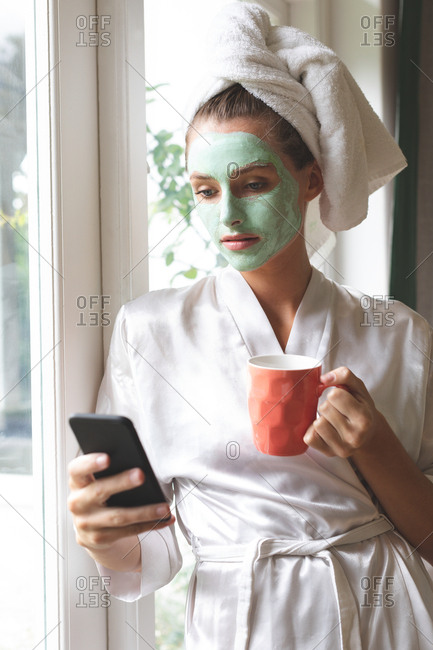 Beautiful woman in face mask using mobile phone near window at home
