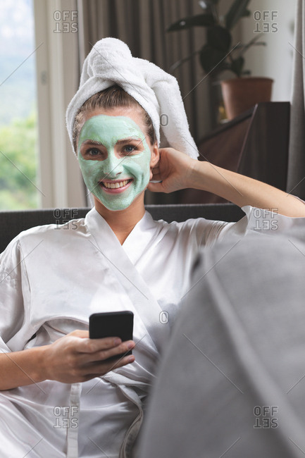 Front view of woman in face mask using mobile phone on sofa at home