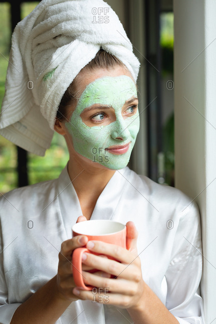 Front view of woman in face mask holding coffee mug at home