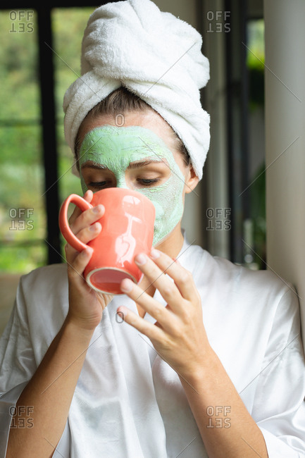 Front view of woman in face mask drinking coffee at home