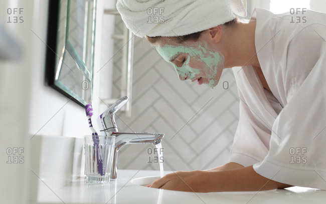 Side view woman washing her face mask in bathroom sink at home