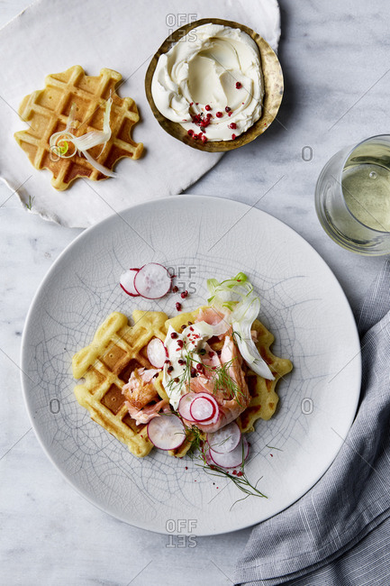 Savory waffles with salmon and cream cheese and a glass of white wine on a marble background.