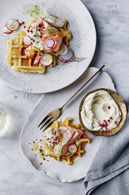 Savory waffles of salmon and cream cheese on a marble background.