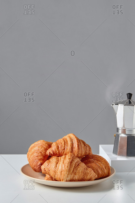 Continental breakfast of tasty homemade french croissants with freshly  coffee in Italian maker on a gray background