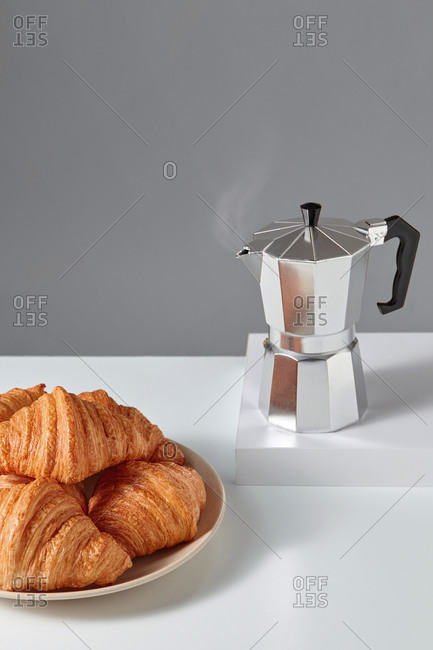 Freshly brewed fragrant coffee with homemade french pastries on a stone table and grey background