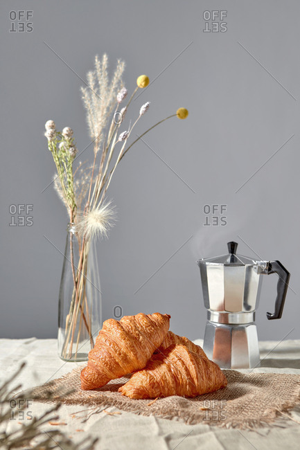 Morning breakfast setting with freshly brewed coffee, delicious homemade french pastries and flower vase on a gray background