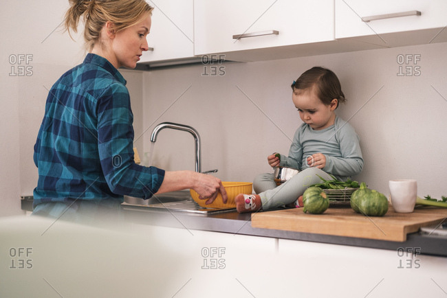 Mother and toddler daughter wash and prepare vegetables in a kitchen