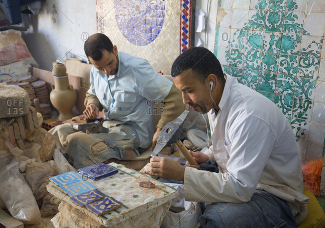 Fes, Morocco - April 6, 2019: Pottery and tile workshop, men making mosaic wall hanging and patio elements for sale to tourists.