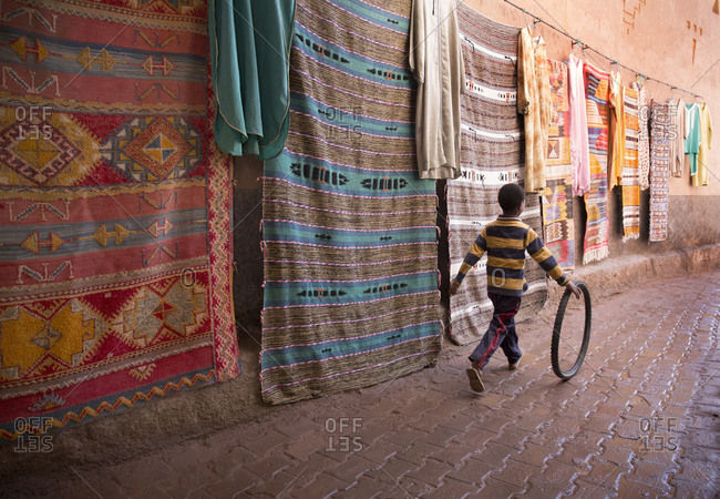 Taourirt Kasbah, Morocco - April 12, 2019: Young boy playing with bicycle tire in market