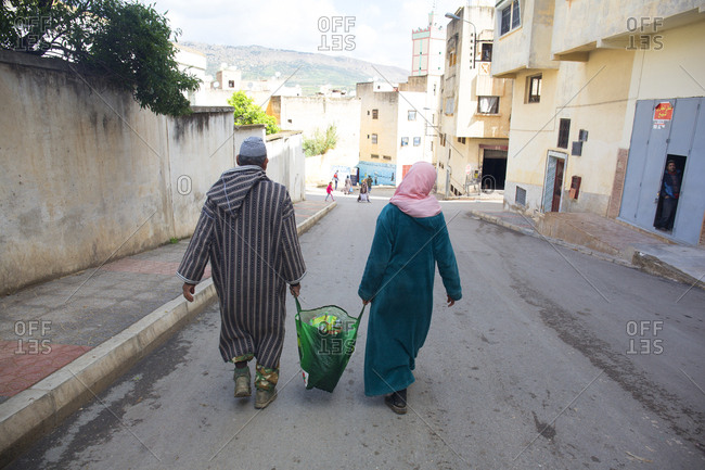 Fes, Morocco - April 6, 2019: Man and woman carrying home shopping bag through the city