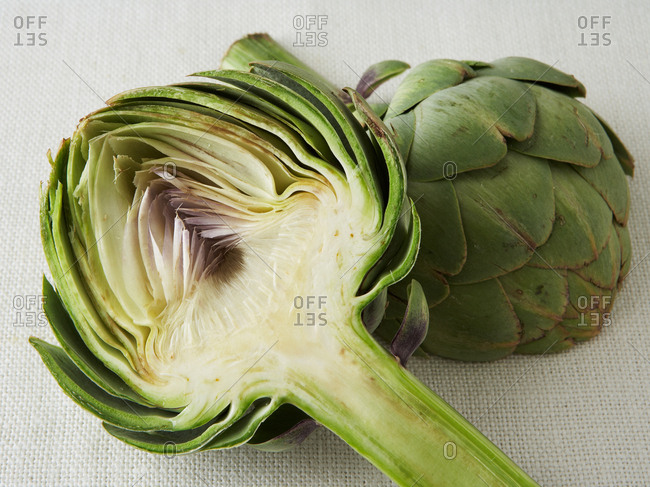 Detailed view of halved artichoke on textured background.