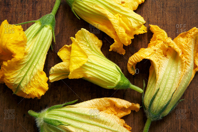 Overhead view of yellow squash blossoms on a dark wood cutting board