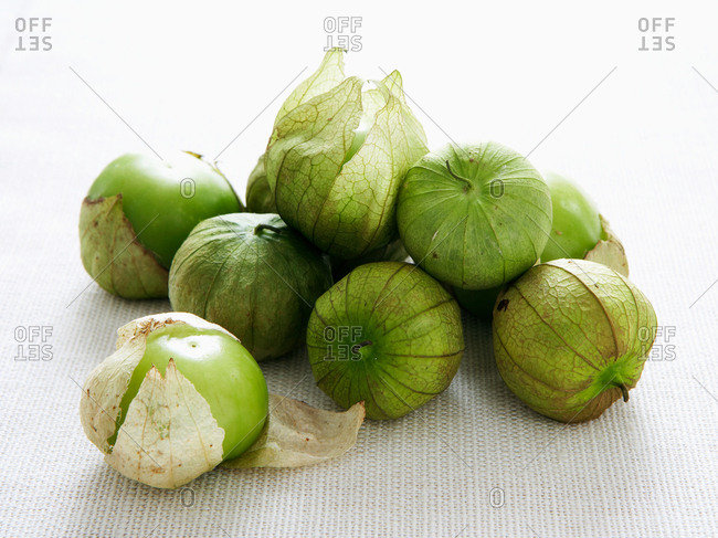 Close-up of green tomatillos on a white textured surface