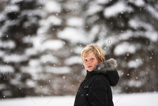 Portrait of a young boy in the snow in the country