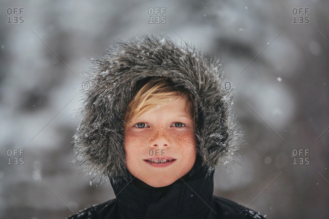 Portrait of a young boy in the snow in the country with his hood on