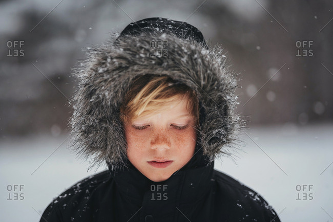 Portrait of a young boy in the snow in the country with his hood on looking down