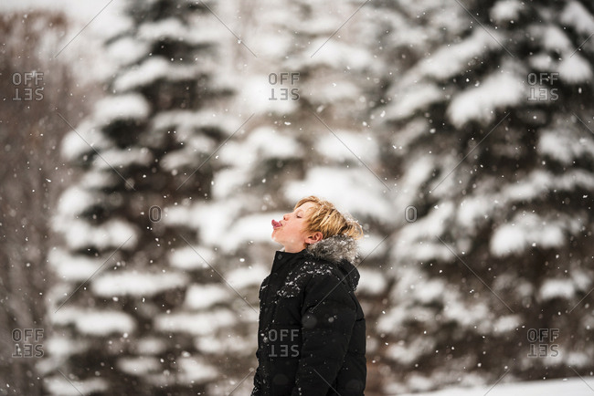 Portrait of a young boy in the snow in the country catching snowflakes with his tongue