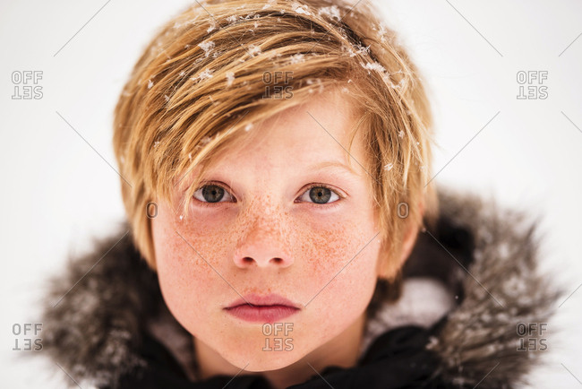 Portrait of a young boy in the snow in the country close up