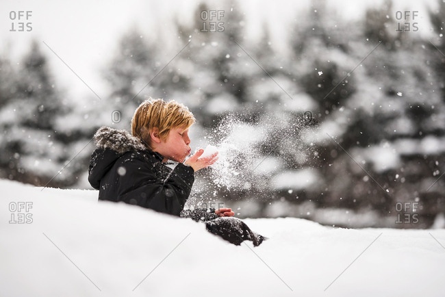 Portrait of a young boy blowing snow from his hands