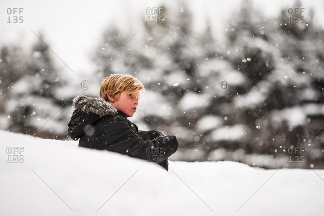 Portrait of a young boy sitting in the snow