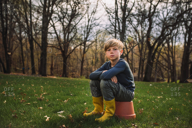 Portrait of a young boy sitting outside in the early spring