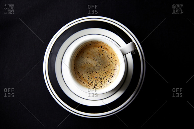Single espresso in a cup and saucer on black tablecloth