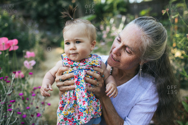 A grandmother holds her baby granddaughter in a garden