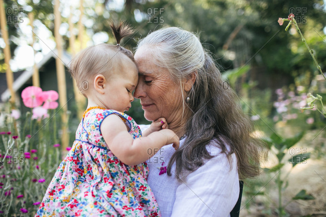 A grandmother and her granddaughter sit in a garden, foreheads together