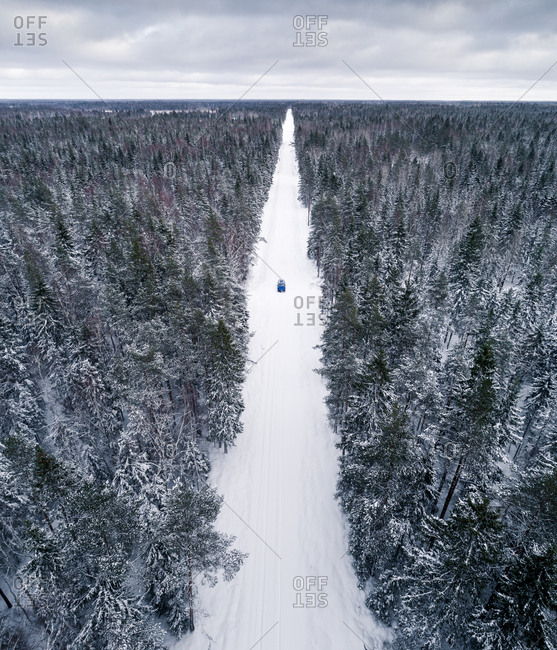 Aerial view of a blue car driving on a snowy straight forest road in Estonia.