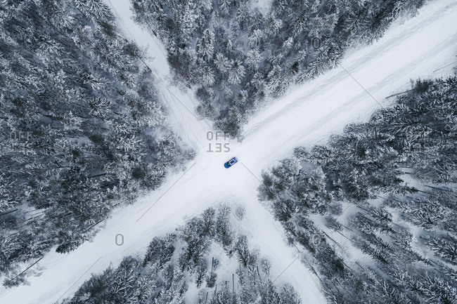 Aerial view of a blue car driving on a snowy forest road in Estonia.
