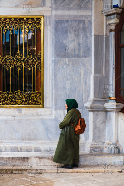 May 16, 2019: Side view of senior muslim female with bag in hijab looking away near ancient marble house at Istanbul, Turkey