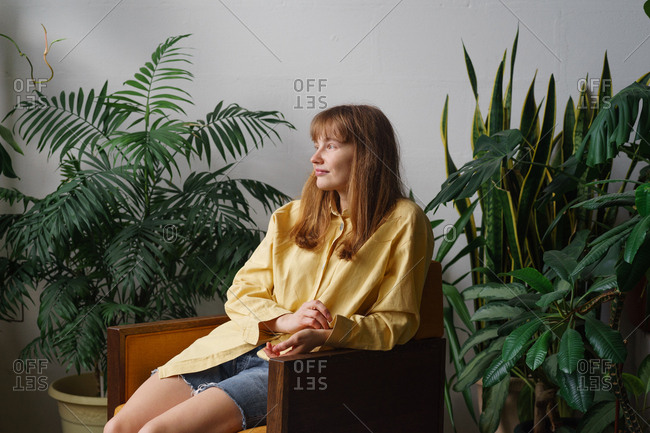 Young woman with ginger hair and freckles dressed in yellow shirt and casual jeans shorts sitting on a chair in a room full of home plants
