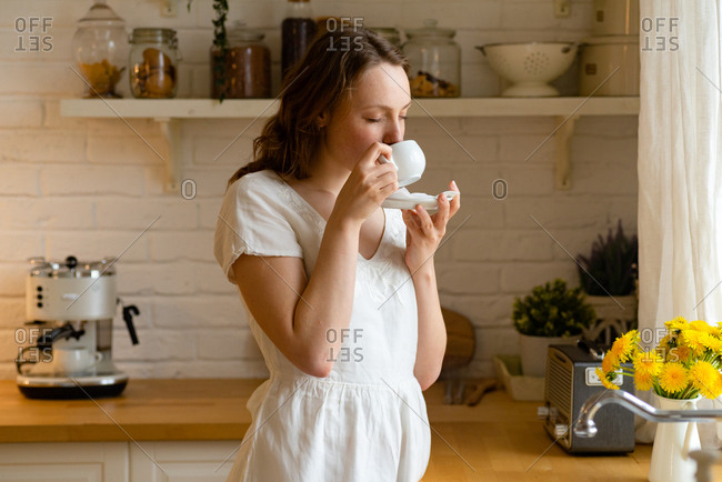 Redhead young woman drinking coffee at the kitchen near the window