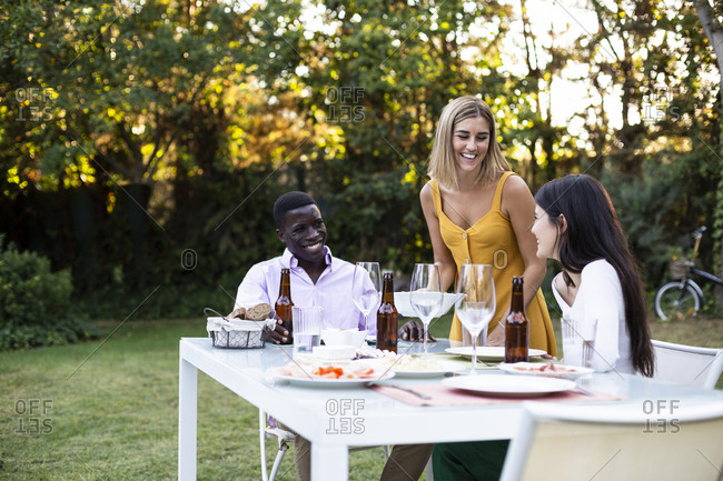 Host serving food at a summer dinner in the garden