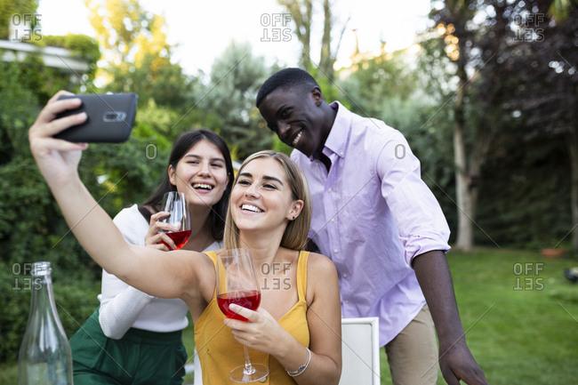Friends having fun at a summer dinner in the garden- taking selfies