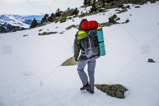 Rear view of man with backpack- snowcapped mountains
