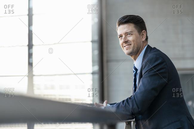 Smiling businessman leaning on railing