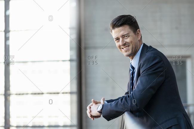 Portrait of smiling businessman leaning on railing