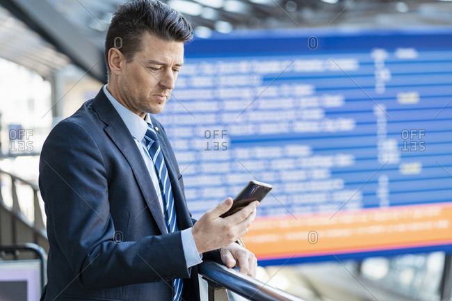 Businessman checking cell phone at the station