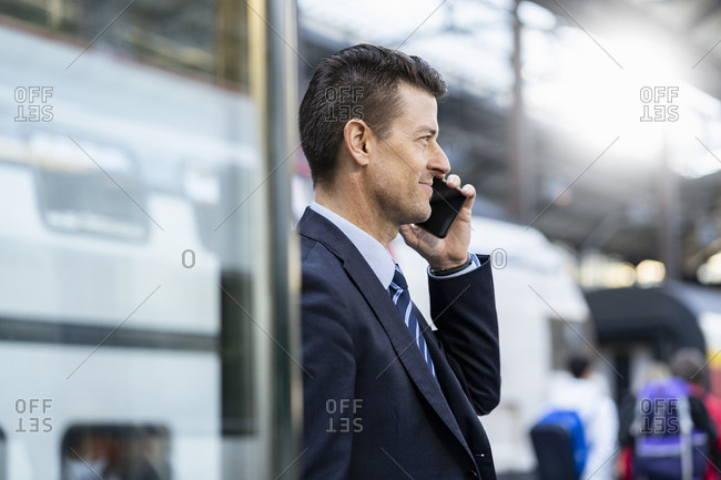 Businessman on cell phone at train station