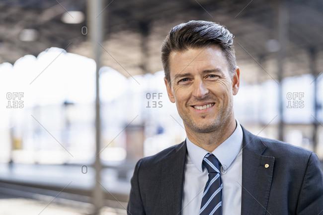 Portrait of smiling businessman at station platform