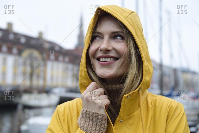 Denmark- Copenhagen- portrait of happy woman at city harbor in rainy weather