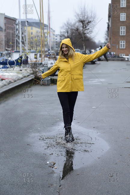 Denmark- Copenhagen- happy woman jumping in puddles at city harbor