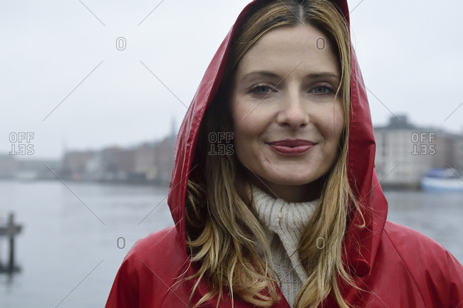Denmark- Copenhagen- portrait of smiling woman at the waterfront in rainy weather